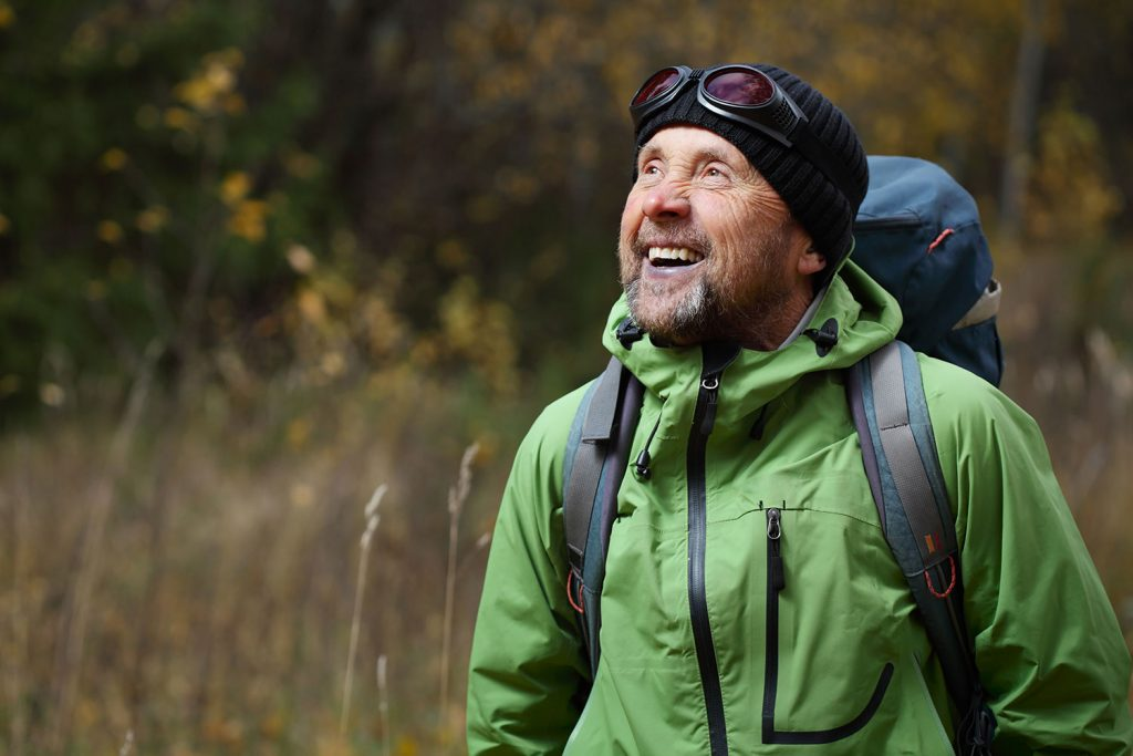An older man smiling while hiking through a forest